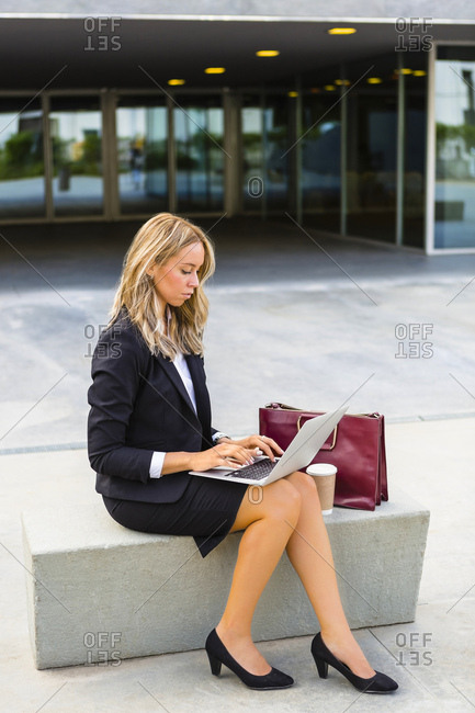 Businesswoman with fashionable leather bag and coffee to go sitting on bench using laptop
