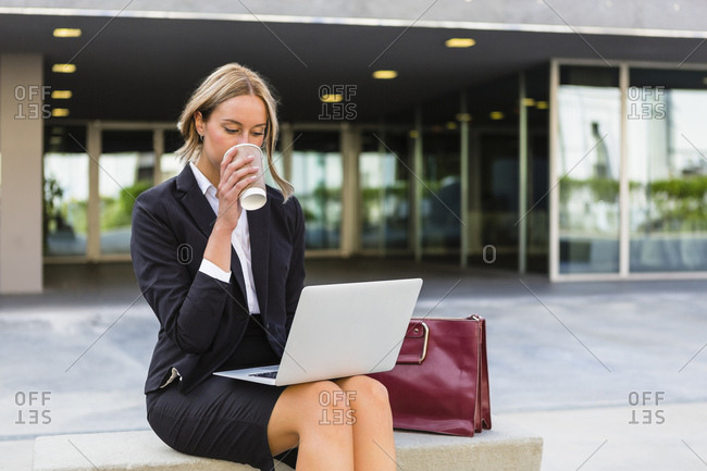 Businesswoman with fashionable leather bag and coffee to go sitting on bench looking at laptop