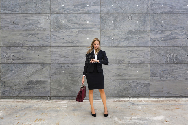 Businesswoman wearing ladies' suit checking the time