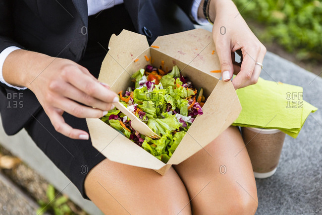 Businesswoman having lunch outdoors- partial view