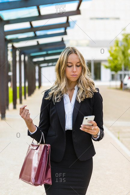 Businesswoman with fashionable leather bag looking at cell phone