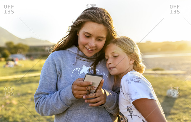 Two girls looking at cell phone outdoors