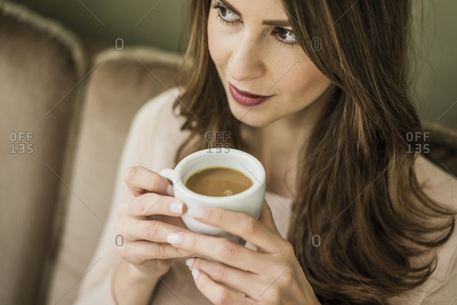 Portrait of woman sitting on couch drinking cup of white coffee