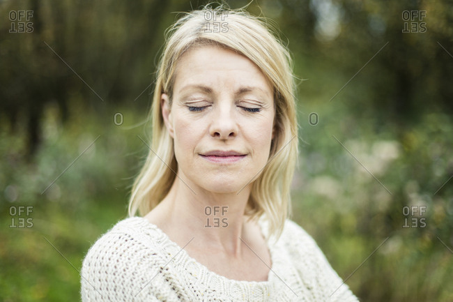 Portrait of blond woman with eyes closed outdoors