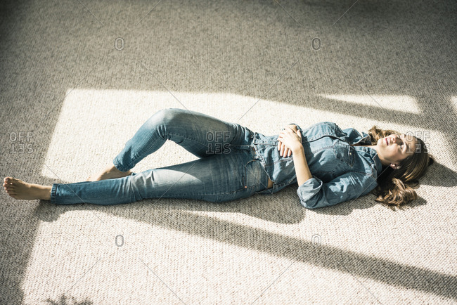 Young woman lying on carpet in the living room enjoying sunlight