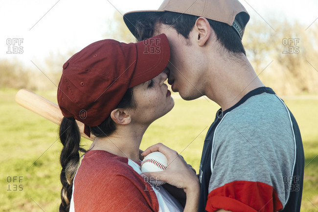 Young couple with baseball equipment kissing in park