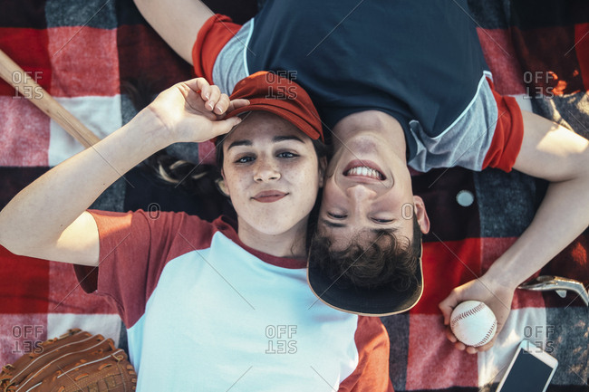 Portrait of smiling young couple with baseball equipment lying on a blanket