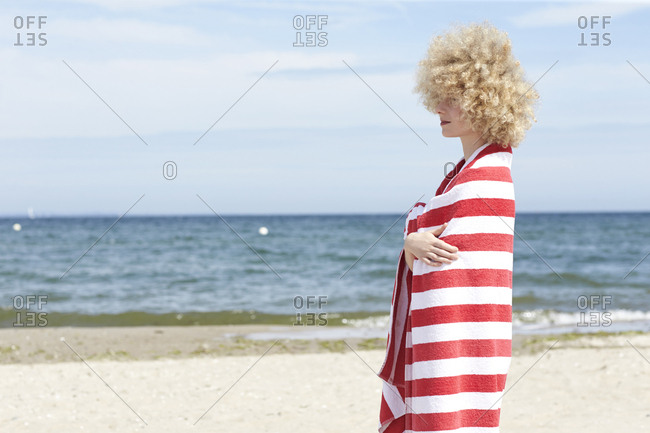 Young woman wrapped in beach towel standing in front of the sea