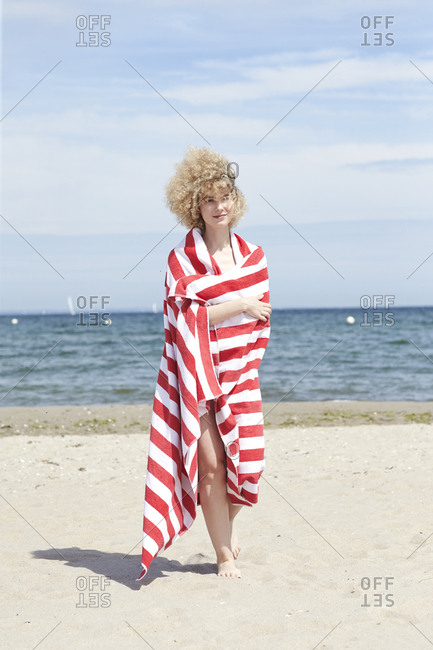 Smiling young woman wrapped in beach towel standing in front of the sea