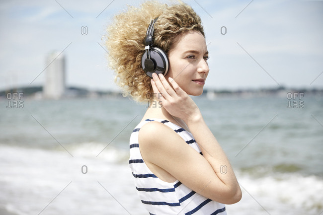 Portrait of young blond woman with headphones on the beach