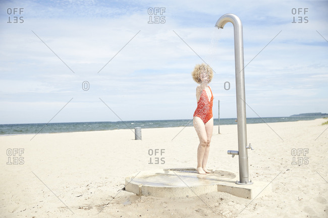 Young woman blond woman taking shower on the beach