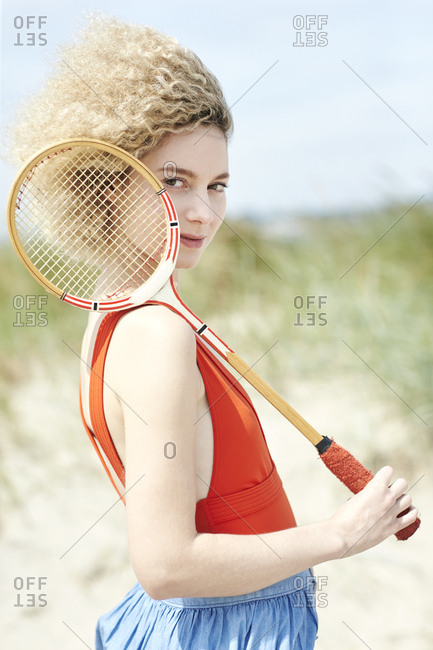 Portrait of young woman with tennis racket on the beach