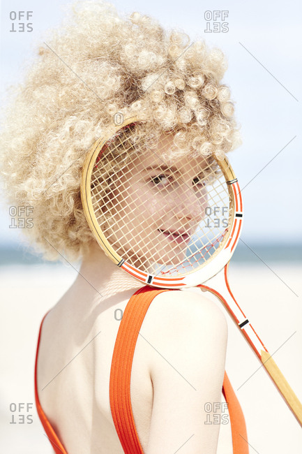 Portrait of young woman looking through reticule of tennis racket on the beach