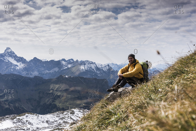Germany- Bavaria- Oberstdorf- smiling hiker sitting in alpine scenery