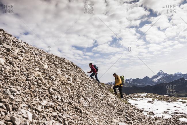 Germany- Bavaria- Oberstdorf- two hikers walking up stony mountain