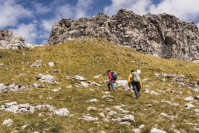 Germany- Bavaria- Oberstdorf- two hikers walking up alpine meadow