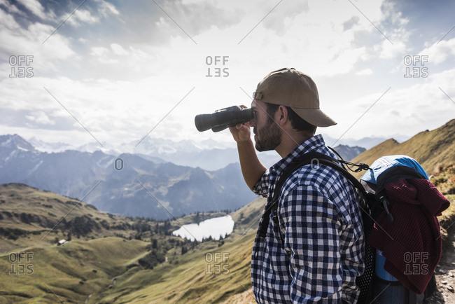 Germany- Bavaria- Oberstdorf- hiker with binoculars in alpine scenery