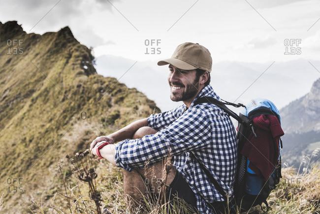 Germany- Bavaria- Oberstdorf- smiling hiker resting on mountain ridge