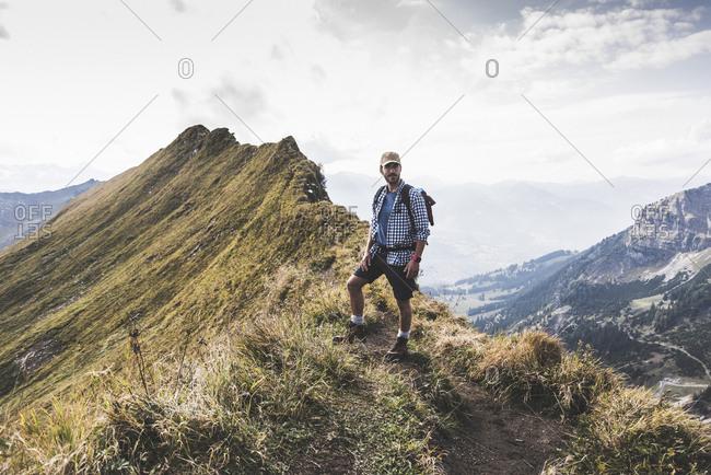 Germany- Bavaria- Oberstdorf- hiker standing  on mountain ridge in alpine scenery