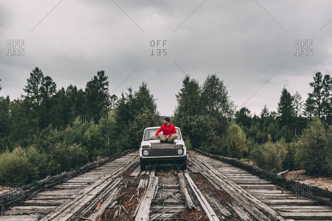 Man sitting on car bonnet on wooden lane in rural landscape
