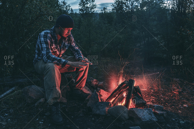 Man sitting at campfire in rural landscape