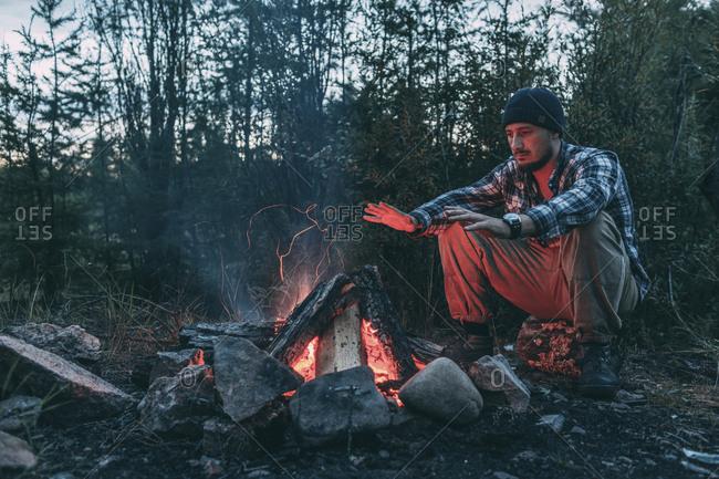 Man sitting at campfire in rural landscape