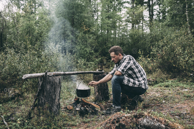 Man cooking in cauldron in rural landscape