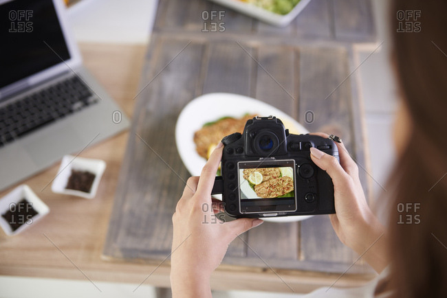 Close-up of woman taking photo of fried fish
