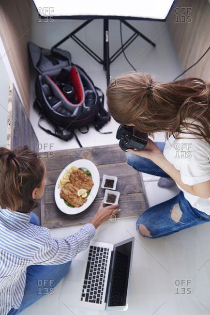 Woman styling prepared dish during photo session