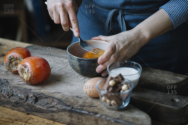 Woman mashing persimmon for preparing dessert