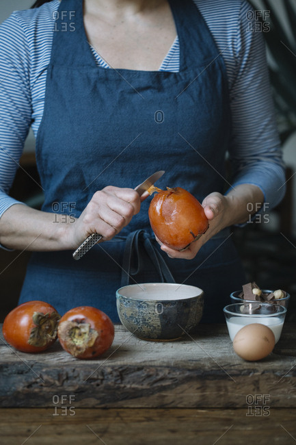 Woman peeling persimmon for preparing dessert- partial view
