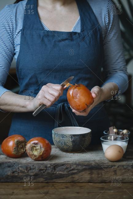 Woman peeling persimmon for preparing dessert- partial view