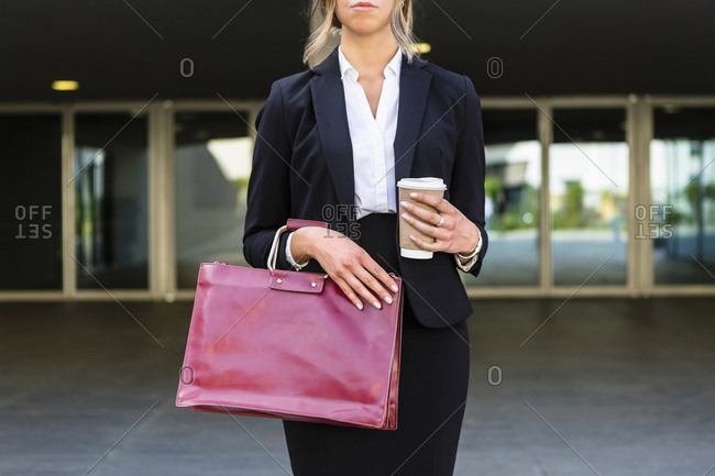 Businesswoman with fashionable red leather bag and coffee to go- partial view