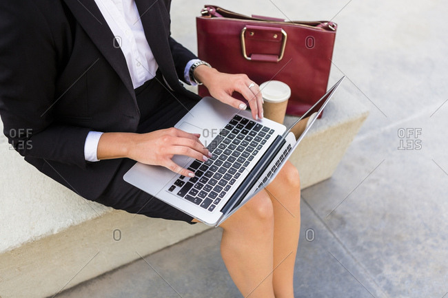 Businesswoman with fashionable leather bag and coffee to go sitting on bench using laptop- partial view