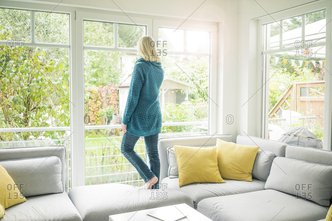 Woman in living room looking out of window
