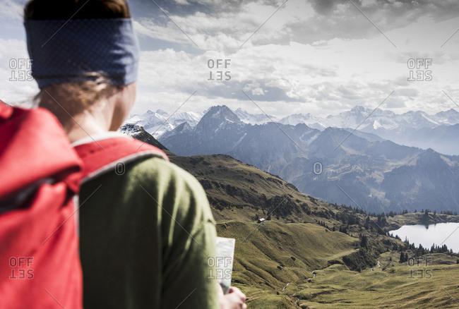 Germany- Bavaria- Oberstdorf- hiker with map in alpine scenery