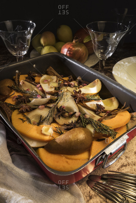 Vegan oven vegetables with pumpkin- pears and spices in roasting tray