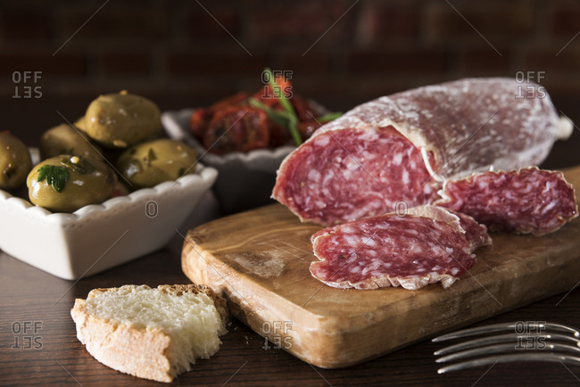 Antipasti- pickled olives- pickled tried tomato- olive bread- salami on chopping board