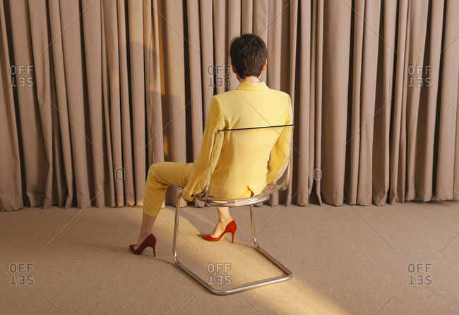 Woman with yellow suit sitting in a chair