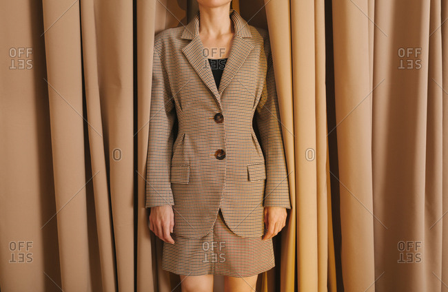 Woman with checkered suit standing in front of curtain