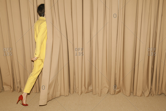 Woman with yellow suit going behind a curtain