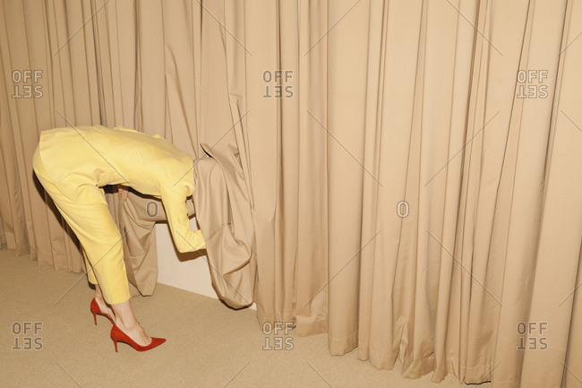 Woman with yellow suit looking under curtain