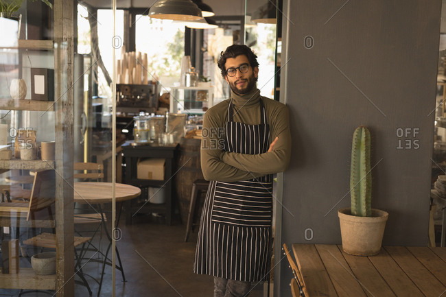 Portrait of waiter standing with arms crossed in coffee shop