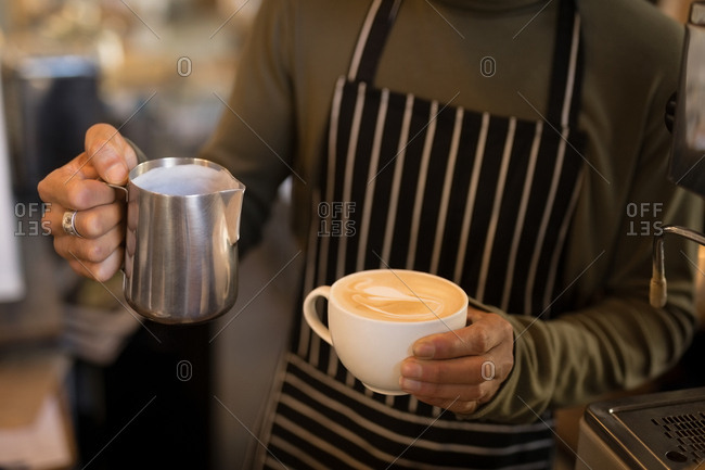 Barista holding cup of coffee and steamed milk jug in coffee shop