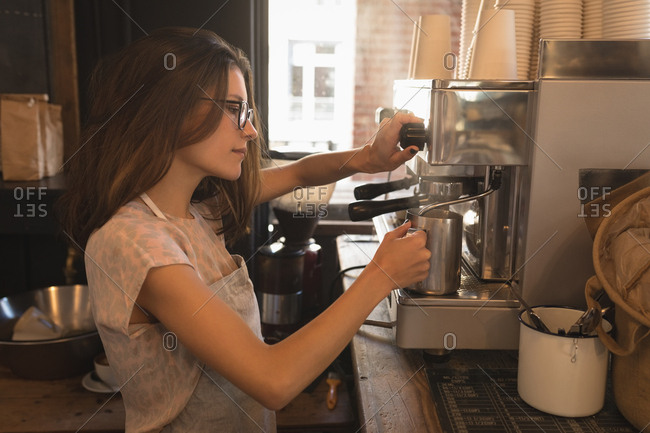 Barista steaming milk at the coffee machine in a cafe