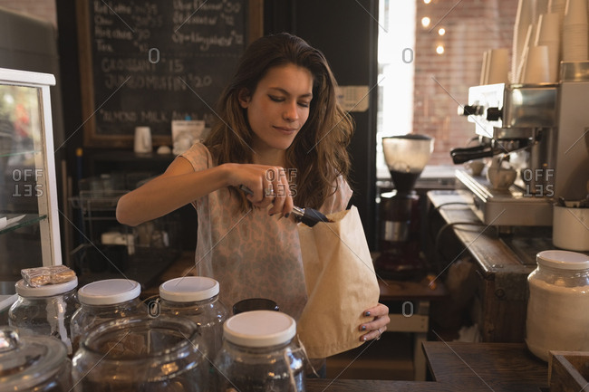 Waitress packing sweet food in paper bag at counter in coffee shop