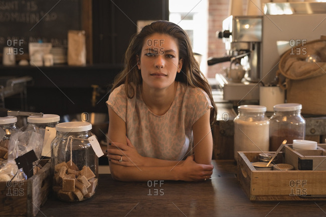 Portrait of waitress standing at counter in the coffee shop