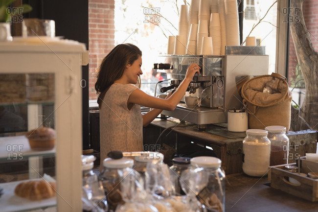 Smiling waitress making cup of coffee in coffee shop