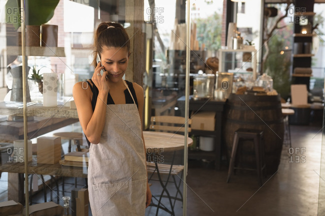 Smiling waitress talking on mobile phone in coffee shop
