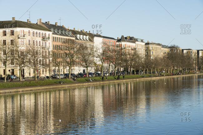 Copenhagen, Denmark - December 4, 2017: Apartment buildings along tree-lined canal